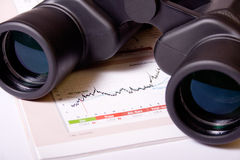 Market Trends Monitoring. Binoculars and table with financial figures royalty free stock image