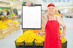 Market vendor holding clipboard in a supermarket. Mature market vendor holding a clipboard in front of an aisle with fruits and vegetables Royalty Free Stock Photos