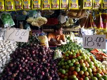 A market vendor inside a fruit and vegetable stall in a public market. stock photography