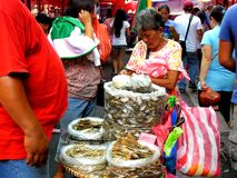 Market vendor selling dried fish in a market in philippines Stock Image