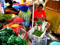 Market vendor selling vegetables in a market in philippines Stock Photo