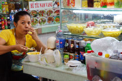 Market vendor takes  quick lunch Royalty Free Stock Images