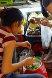 Market vendor takes  quick lunch Stock Photo
