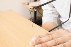 Marketeriehandwerker, der mit seinem Sawing arbeitet stockbild