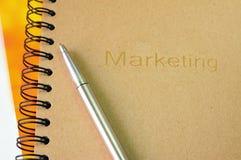 Marketing-Buch mit silbernem Stift Stockfotografie
