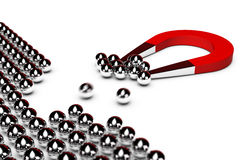 Marketing campaign, business success. Red horseshoe magnet attracting some chrome balls from a crowd, white background Stock Images