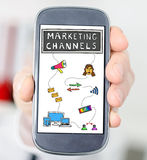 Marketing channels concept on a smartphone. Hand holding a smartphone with marketing channels concept stock photo