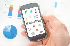 Marketing concept on a smartphone. Held by a hand stock photos