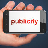 Marketing concept: smartphone Publicity. Marketing concept: hand holding smartphone with word Publicity on display. Generic mobile smart phone in hand on Dark Stock Photography