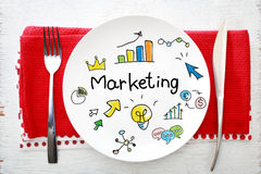 Marketing concept on white plate with fork and knife Royalty Free Stock Photos