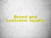 Marketing concept: Brand and Customer loyalty on wall background. Marketing concept: Yellow Brand and Customer loyalty on textured concrete wall background stock images