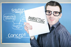 Marketing man displaying business plan for success. Humorous portrait of an education marketing man wearing dork glasses displaying business plan for strategy Stock Photography
