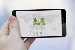 Marketing online cell phone. Communications and marketing concept: hand holding an online marketing 3d generated smartphone. Screen graphics are made up stock photography