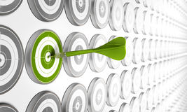 Marketing plan. Green target hitted by a green dart with many other grey targets around Royalty Free Stock Images