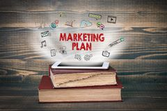 Marketing Plan. Concept cloud coming from screen of the phone, books on the desk Royalty Free Stock Images