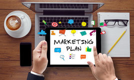 Marketing Plan concept. Message on tablet pc screen held by businessman hands - concept, top view computer, phone ,coffee, Warm tone royalty free stock images