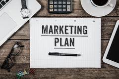 Marketing Plan text on note pad, Office desk with computer technology, high angle. Marketing Plan written on note pad, office desk with electronic devices royalty free stock images