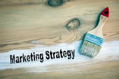 Marketing Strategy Business concept. Paintbrush with white colour on a wooden background stock images