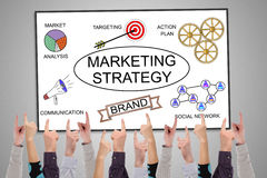Marketing strategy concept on a whiteboard. Pointed by several fingers Royalty Free Stock Photos
