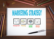Marketing Strategy. Notebooks, pen and colored pencils on a wooden table Royalty Free Stock Photography