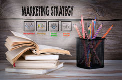 Marketing Strategy. Stack of books and pencils on the wooden table. Royalty Free Stock Photos