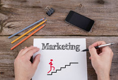 Marketing strategy stairs. Text on a sheet of paper. On wooden o. Ffice desk smartphone, pencils, clip Stock Images