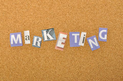 Marketing Word Made From Newspaper Letter. Shot over pinboard background Royalty Free Stock Photos