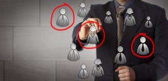 Marketingspezialist Selecting Three Prospects in einer Gruppe Lizenzfreie Stockfotos