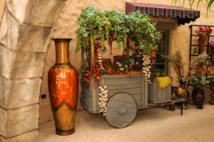 Marketplace. A rustic wooden cart filled with fruits and vegetables in the marketplace with a huge vase in the foreground royalty free stock image