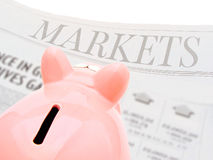 Markets. Piggy bank reading the Markets section of a newspaper Stock Photos