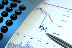Markets Go Down. Financial chart, market's falling, calculator, pen, cross key lighting with blue gel left Stock Image