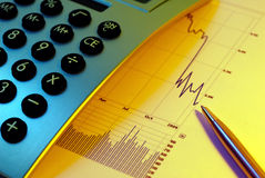 Markets Go Down. Financial chart, market's falling, calculator, pen, cross key lighting, blue gel left, yellow gel right Royalty Free Stock Photo
