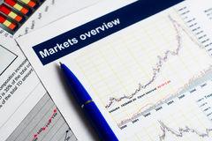 Markets overview report. Closeup of markets overview report and blue pen Royalty Free Stock Images