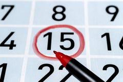 Markiera pióro nad kalendarzem z fifteenth dniem miesiąc podkreślający czerwonym okręgiem zdjęcia stock