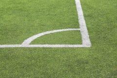 Markierende weiße Farbe einer Ecke auf einem grünen Rasen des Fußballplatzes stockfotografie