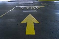Markierungen einer große gelbe Pfeilstraße, die auf ein Stoppschild zeigen lizenzfreie stockbilder
