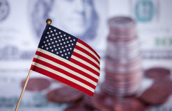Markierungsfahne über Dollarbanknoten und -münzen. Stockbild