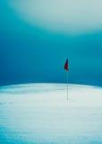 Markierungsfahne auf schneebedecktem Golfplatz Stockfotografie