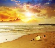 Markierungsfahne in der Flasche auf Strand mit Sonnenuntergang Lizenzfreie Stockfotos