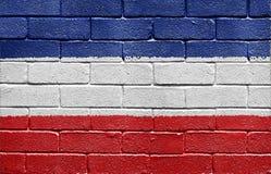 Markierungsfahne des Königreiches von Jugoslawien auf Backsteinmauer Stockbilder