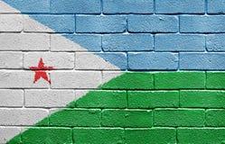 Markierungsfahne von Djibouti auf Backsteinmauer stockfotos