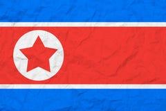 Markierungsfahne von Nordkorea Abbildung der roten Lilie Alte Wandbeschaffenheit Verblaßter Hintergrund stockbilder