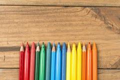 Markierungsstifte und farbige Bleistifte auf hölzernen Brettern stockbild