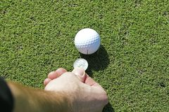 Marking. A golfball with a quarter Stock Photo