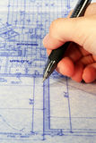 Marking Blueprint. Hand holding a pen to a blueprint Stock Images