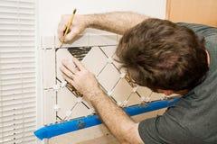 Marking Ceramic Tile. Tile setter marking ceramic tiles for installation Stock Image