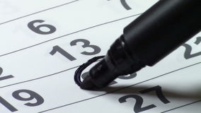Marking the date on the calendar. Paper calendar with numbers on columns and rows representing the days of the month, one of them being encircled with a black