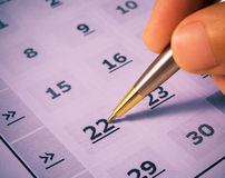 Marking day in calendar. A hand with a pen marking a day in paper calendar Royalty Free Stock Images