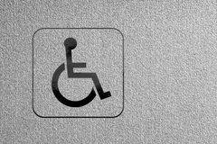 Marking disability. Silver surface to which is attached a symbol of disabled Stock Photos