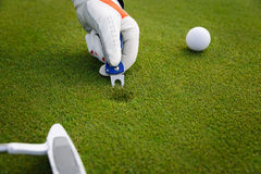 Marking golf ball position at the green. Focus on marker. Stock Photo